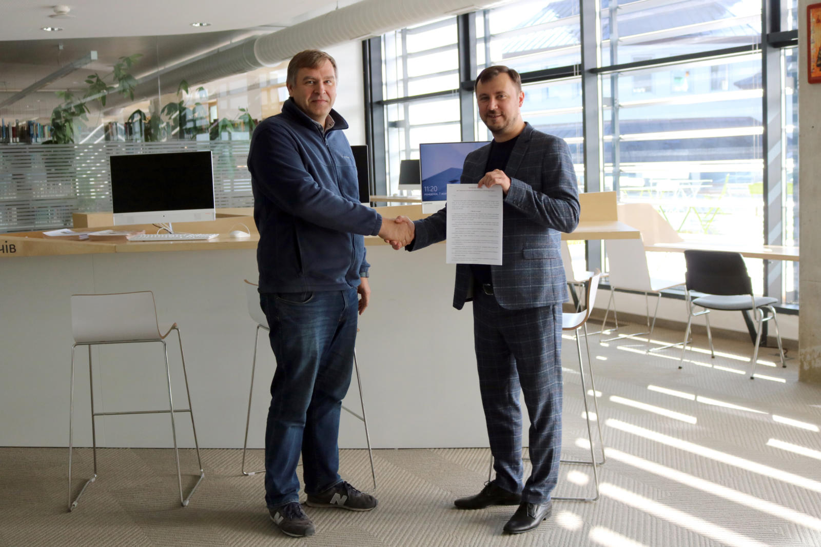 Yaroslav Prytula, Dean of Faculty of Applied Sciences at UCU (to the left), and Ihor Salamin, Human Capital Director at PLVision (to the right), welcome the signing of the collaboration agreement between their organizations.